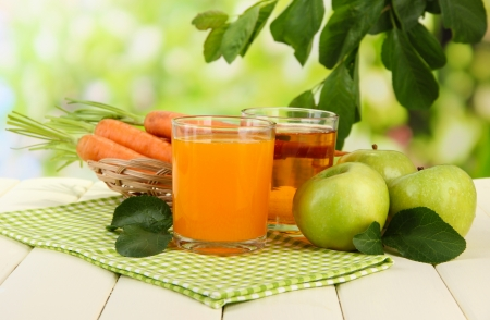 Glasses of juice, apples and carrots on white wooden table, on green background photo