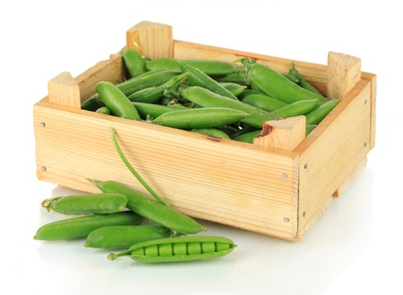 Sweet green peas in wooden box isolated on white photo