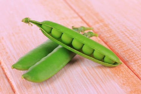 Sweet green peas on wooden background photo