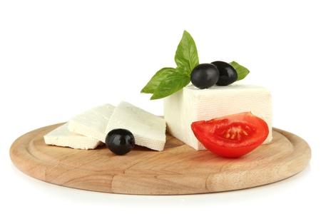 queso de cabra: Queso de oveja leche con albahaca y aceitunas negras, tomate en la tabla de cortar, aislado en blanco Foto de archivo