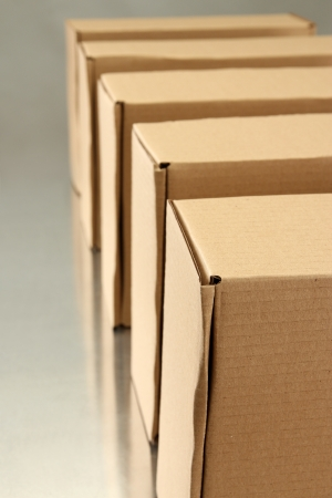 Cardboard boxes on conveyor belt, on grey background photo