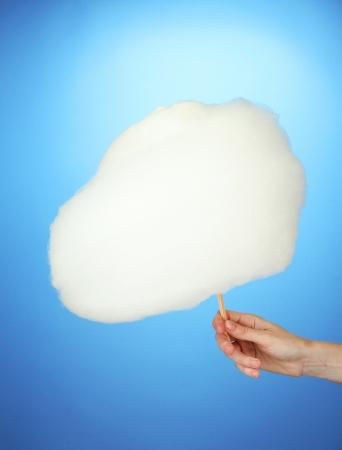 algodon de azucar: Mano que lleva a seguir con algodón de azúcar, el color de fondo Foto de archivo
