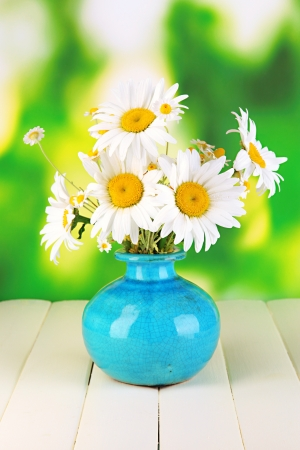 amorousness: Beautiful bouquet chamomiles in vase on wooden table on natural background