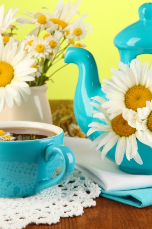 Beautiful bouquet chamomiles in teapot on wooden table on natural background photo