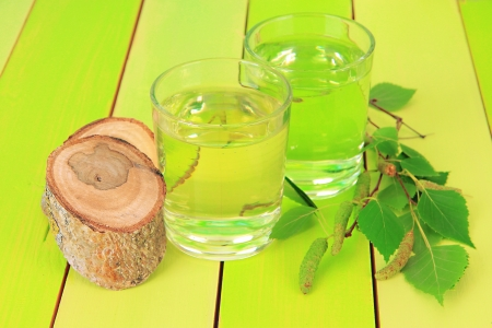 sap: Glasses of birch sap on green wooden table