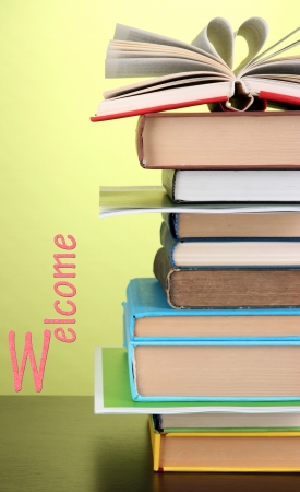 Stack of interesting books and magazines on wooden table on green background photo