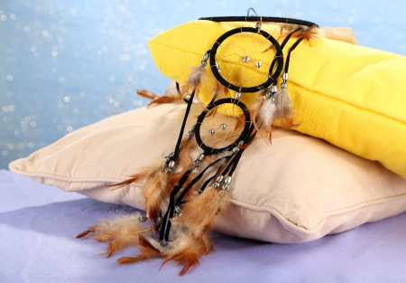 Beautiful dream catcher and pillows on blue background photo