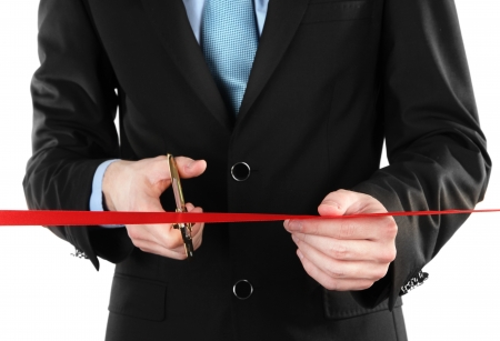 Businessman cutting red ribbon with pair of scissors close up Stock Photo - 20209947