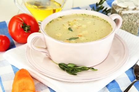 sopa de pollo: Sopa nutritiva en el molde de color rosa en la mesa de madera de cerca