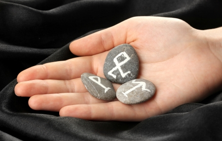 Fortune telling  with symbols on stone in hand on black fabric background Stock Photo - 20210042