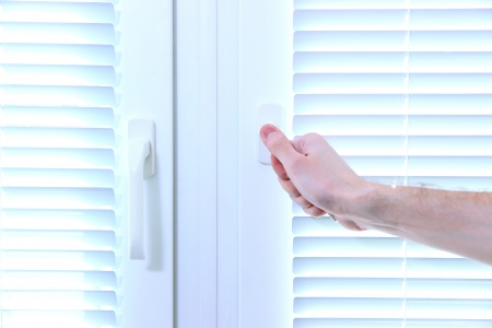 Someone opens metal-plastic window blinds closed Stock Photo - 20213831