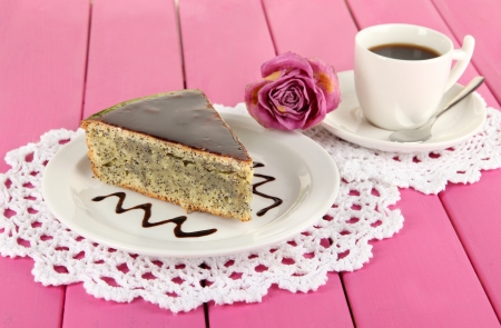 Delicious poppy seed cake with cup of coffee on table close-up photo