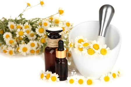 Essential oil and chamomile flowers in mortar isolated on white photo