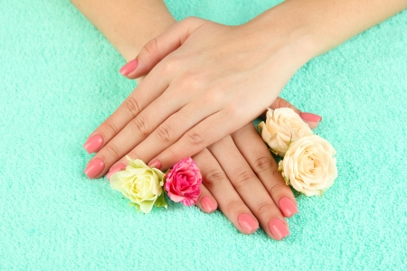 Woman hands with pink manicure and flowers, on color background Stock Photo - 20251338