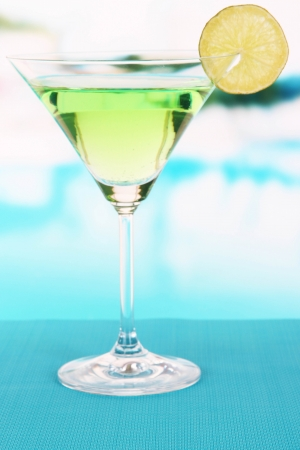 Green cocktail with lime on table on bright background photo