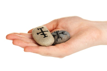 Fortune telling  with symbols on stone in hand isolated on white photo