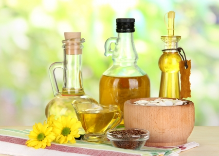 Useful linseed oil and pumpkin seed oil on wooden table on natural background photo