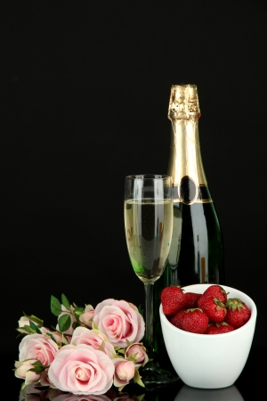 Romantic still life with champagne, strawberry and pink roses, isolated on black photo