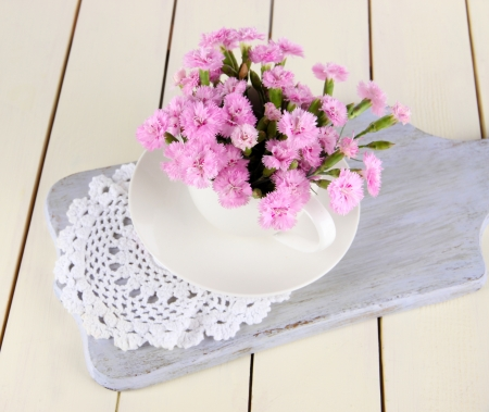 Many small pink cloves in cup on wooden board on beige background photo