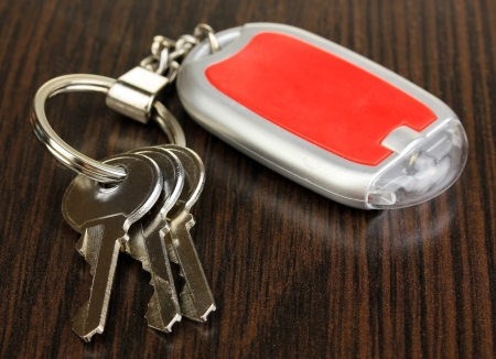 trinket: House keys and keychain on wooden background Stock Photo