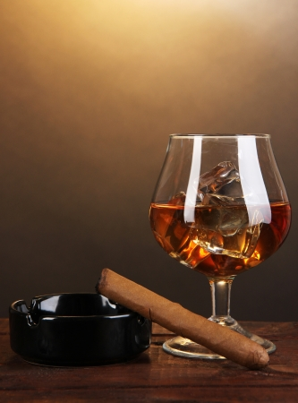 drunks: Brandy glass with ice and cigar on wooden table on brown background