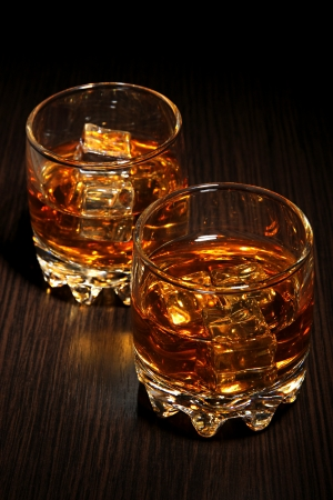 drunks: Brandy glasses with ice on wooden background Stock Photo