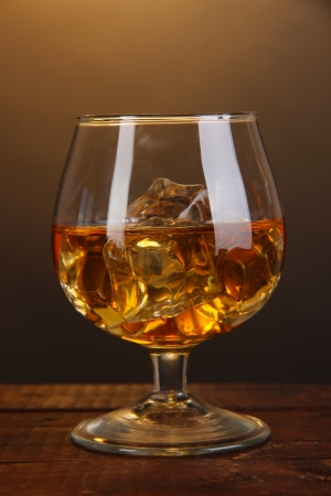 Brandy glass with ice on wooden table on brown background photo