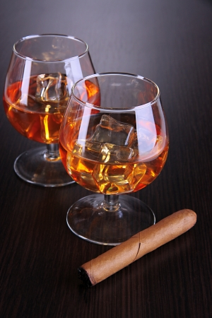 Brandy glasses with ice on wooden background photo
