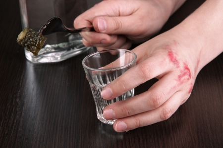 Injured hand hold an alcohol vodka drink glass close-up photo