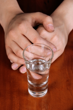 Glass cup filled with vodka at table close-up photo