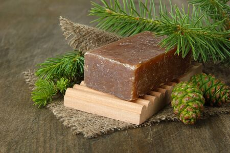 Hand-made soap and green pine cones on wooden background photo