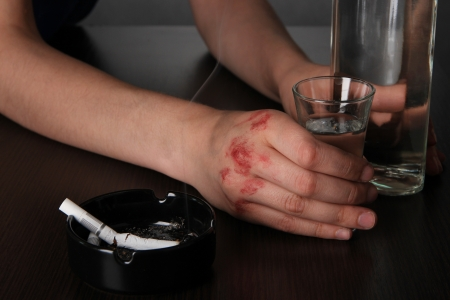 Injured hand hold an alcohol drink glass close-up photo
