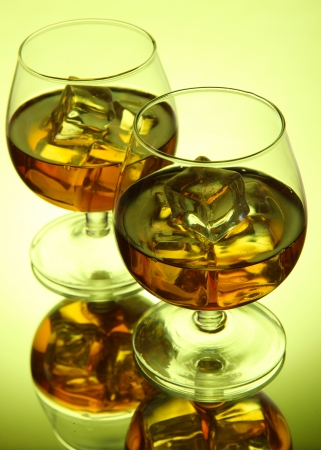 drunks: Brandy glasses with ice on green background