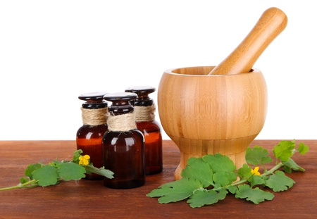 pounder: Blooming Celandine with medicine bottles on table on white background
