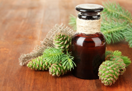 Bottle of fir tree oil and green cones on wooden background photo