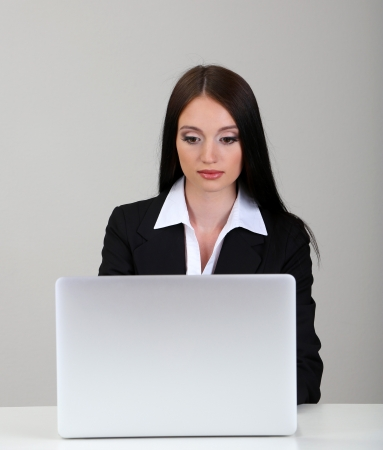 office work: Young business woman working with computer, on gray background