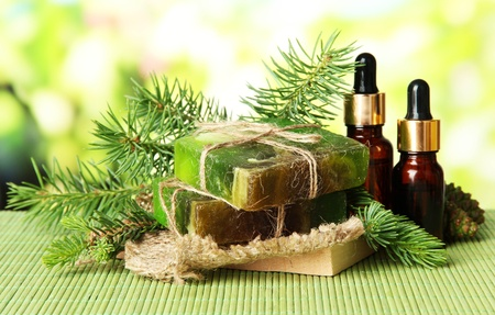 Hand-made soap and bottles of fir tree oil on bamboo mat photo