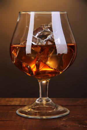 Brandy glass with ice on wooden table on brown background Stock Photo