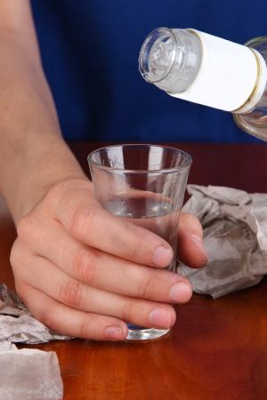 Drunk man drinks vodka at table close-up photo