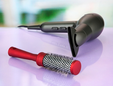 hair dryer and comb brush, on table in beauty salon photo