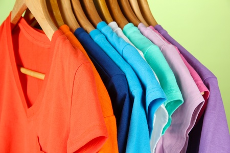 clothing rack: Variety of casual shirts on wooden hangers,on blue background