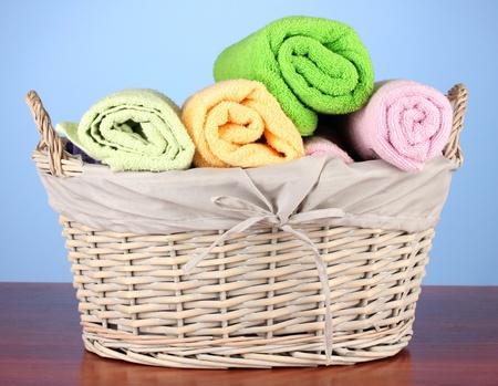 prádlo: Barevné ručníky v koši na barevném pozadí Reklamní fotografie