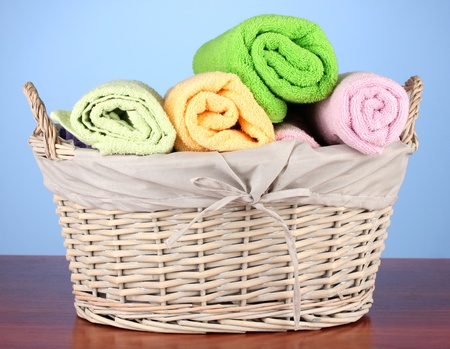 laundry basket: Colorful towels in basket on color background Stock Photo