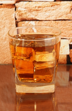Glass of whiskey and ice on brick wall background photo