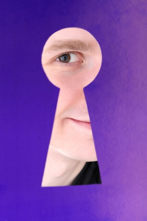 Man eye looking through hole in keyhole, on blue background photo
