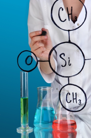 Chemist woman writing formulas on glass on blue background photo