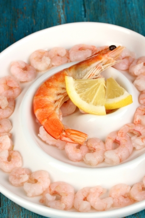 Shrimps with lemon on plate on blue wooden table close-up photo