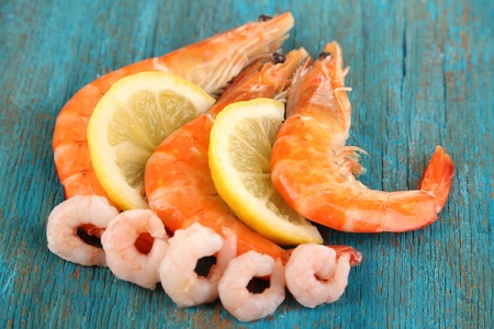 Shrimps with lemon on blue wooden table photo