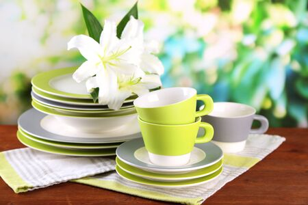 Empty plates and cups on wooden table on green background photo
