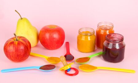 Baby puree in spoons with nipple and fruits on pink background photo